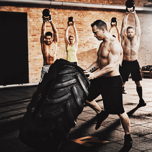 a man lifting a tire with four people working out with kettlebells